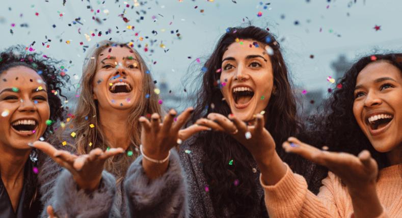 cztery szczęśliwe kobiety zdmuchujące brokat z dłoni